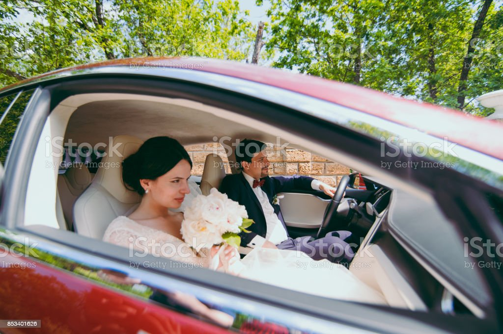 Bride and groom are sitting in the red car salon stock photo