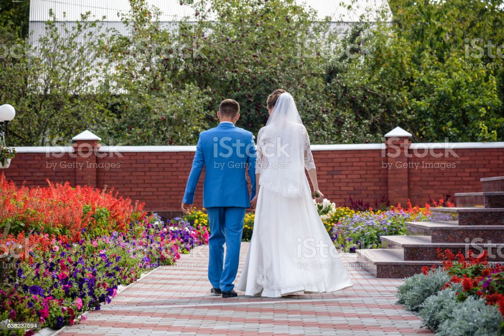 Bride and Groom are walking away in garden. stock photo