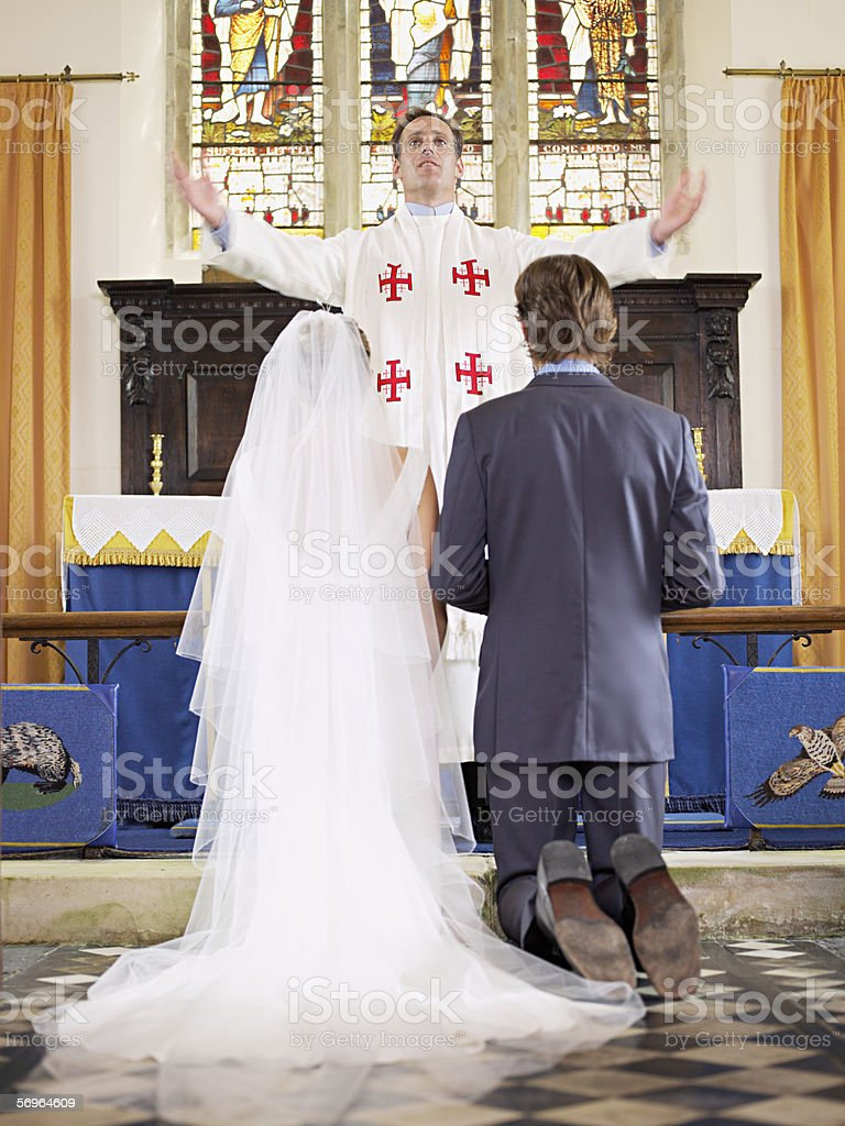 Bride and groom before vicar in church royalty-free stock photo