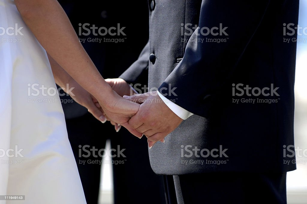 Bride and Groom Close on Hands during Wedding Ceremony stock photo