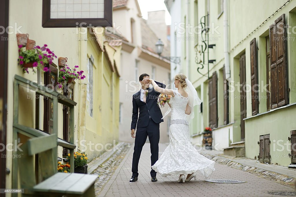 Bride and groom dancing outdoors stock photo