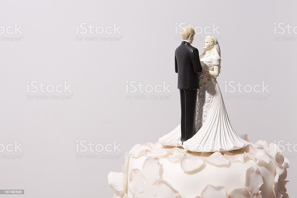 Bride and groom decorations on top of a wedding cake stock photo