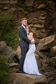 bride and groom embrace on a background of wild rocks