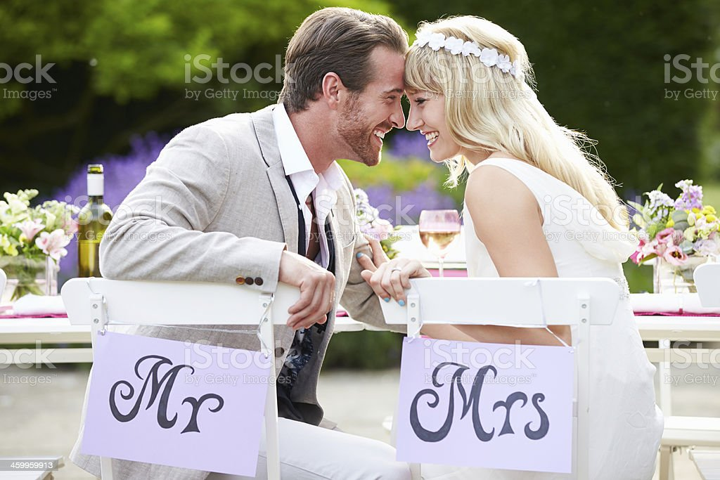Bride And Groom Enjoying Meal At Wedding Reception stock photo