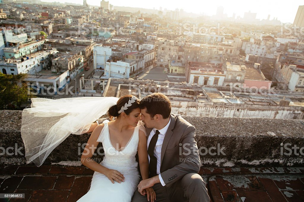Bride and groom enjoying time together on rooftop stock photo