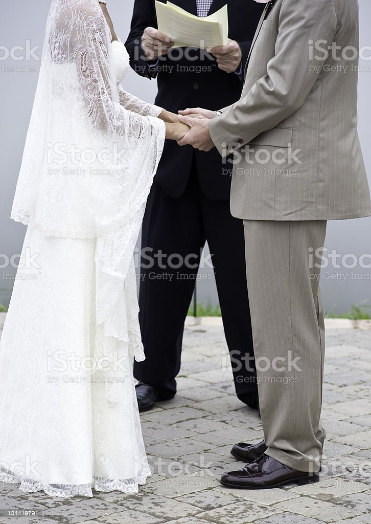 Bride and Groom Exhange Vows While Holding Hand at Wedding royalty-free stock photo