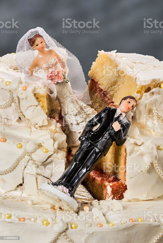 Bride and groom figurines collapsed at ruined wedding cake stock photo