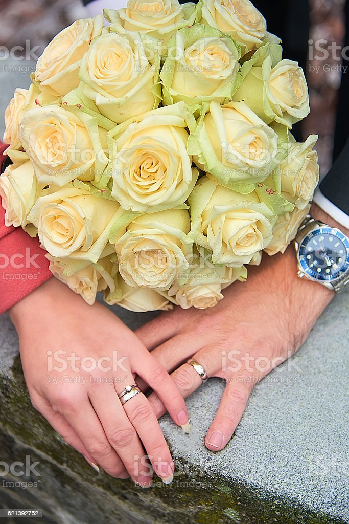 Bride and groom hands with flowers stock photo