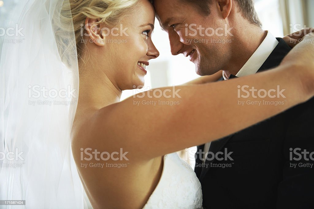 A bride and groom happily looking at each other stock photo