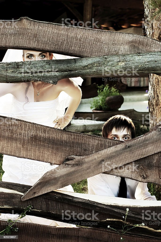 bride and groom hiding stock photo