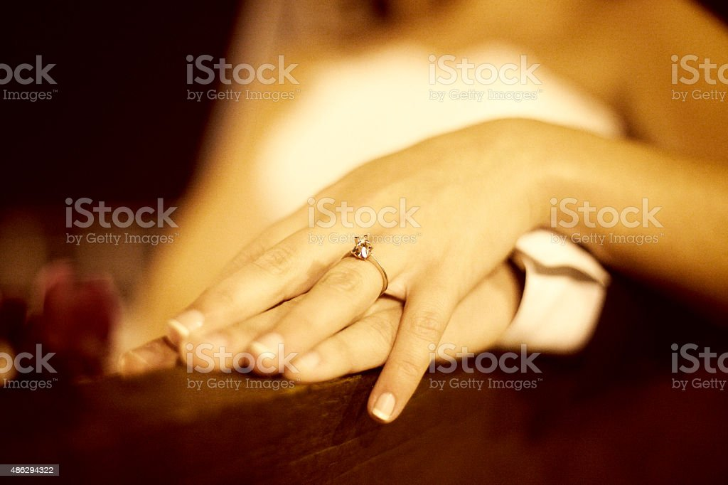 Bride and groom holding hands during their wedding ceremony stock photo