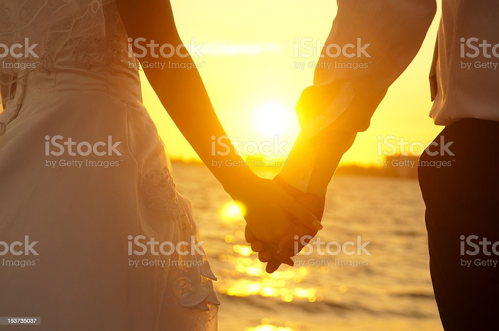 Bride and groom holding hands in front of a sunset stock photo