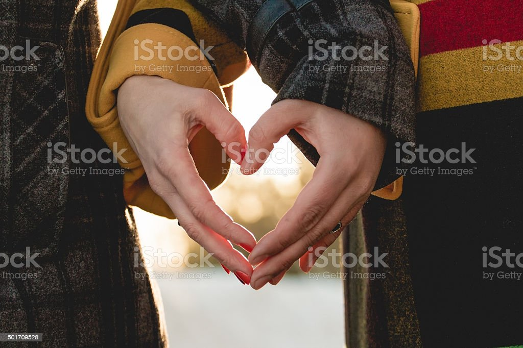 bride and groom holding hands in shape of heart stock photo