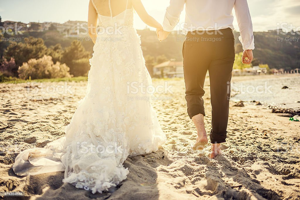 Bride and groom holding hands on the beach at sunset stock photo