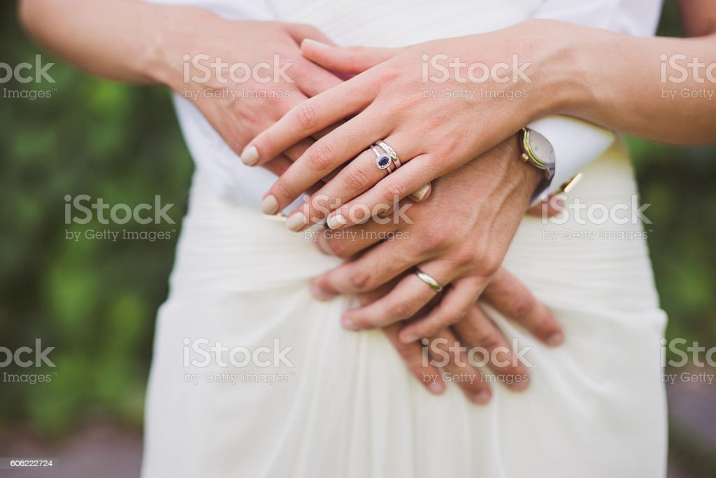bride and groom holding hands, wedding rings on their fingers stock photo