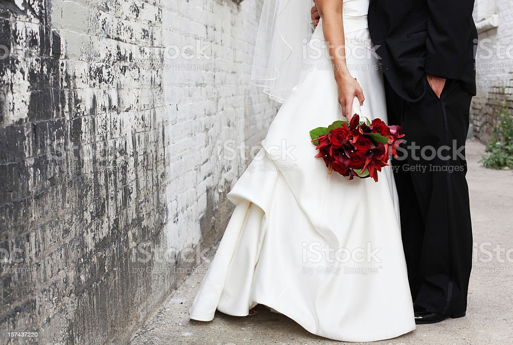 Bride and Groom in alley, Red bouquet stock photo