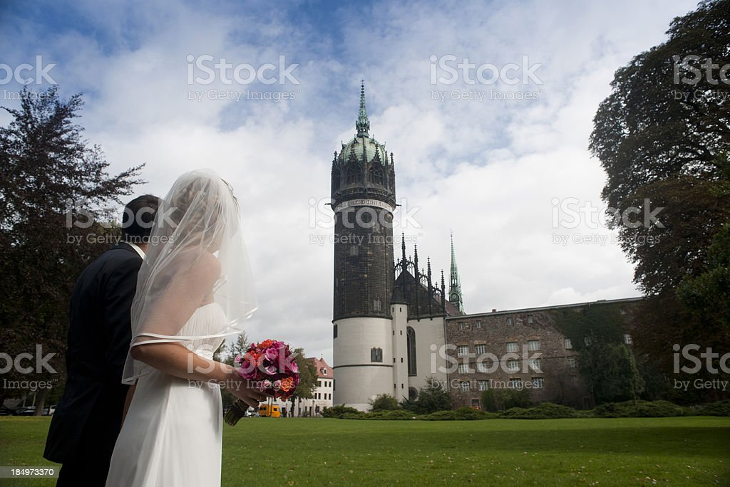 Bride and groom in front of church stock photo