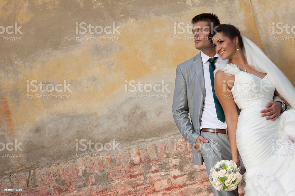 Bride and groom in front of the yellow wall stock photo