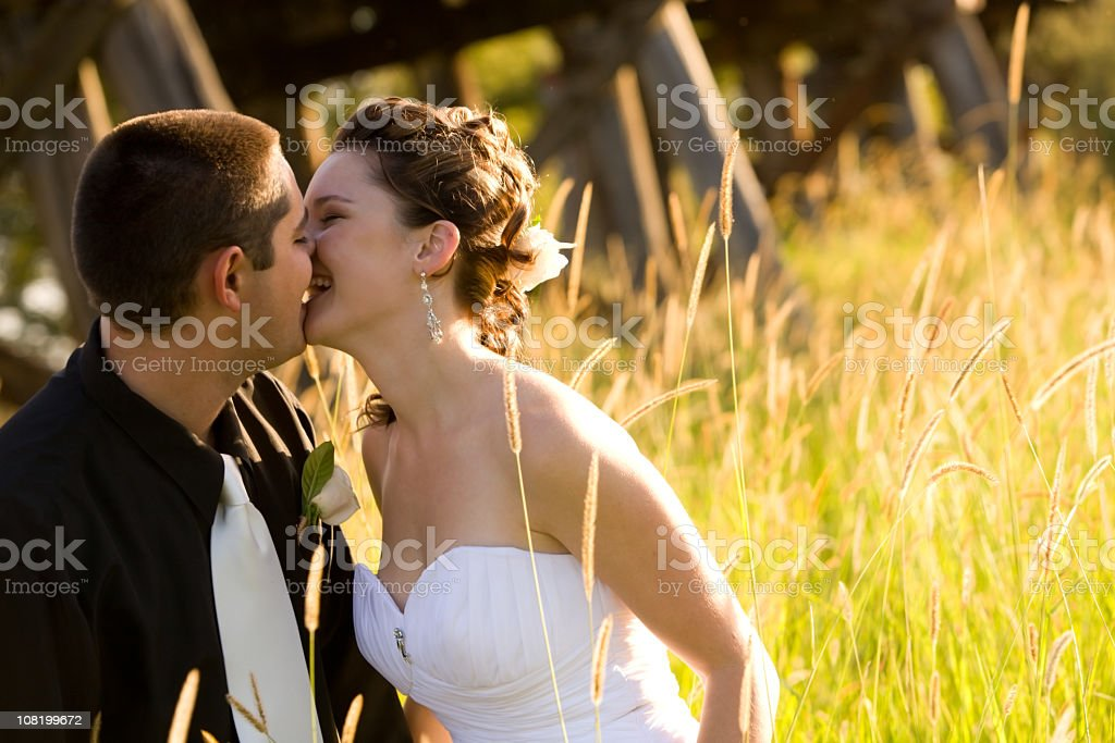 Bride and Groom Kissing at Sunset stock photo