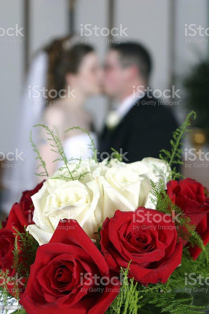 Bride and groom kissing behind wedding flowers royalty-free stock photo