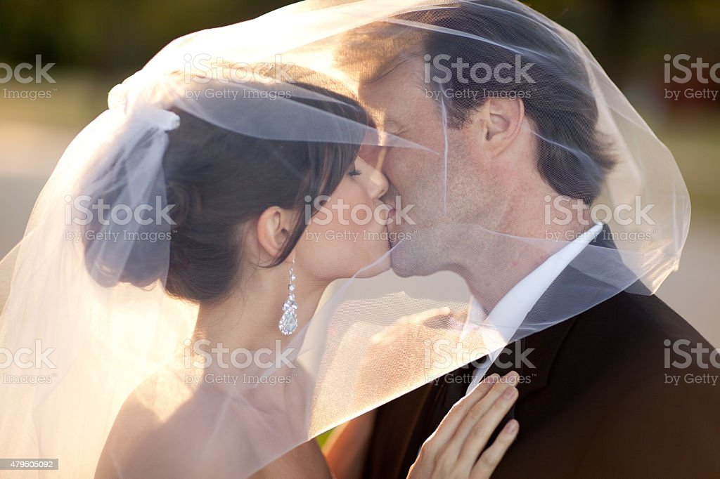 Bride and Groom Kissing Behind Wedding Veil Outside stock photo