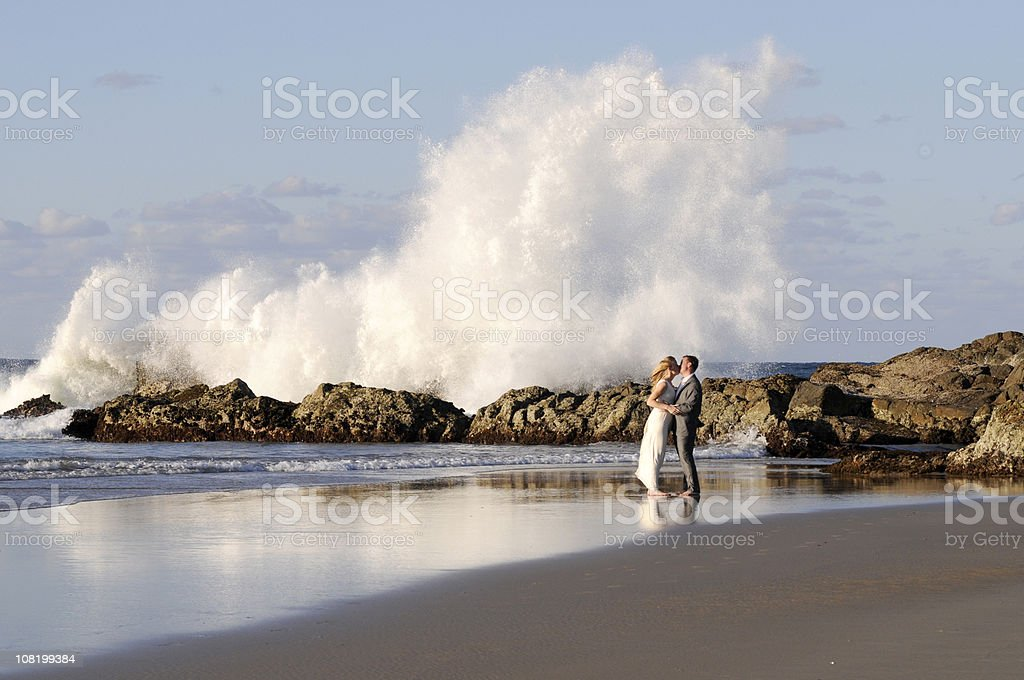 Bride and groom kissing in front of huge crashing wave stock photo