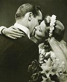 Bride and Groom kissing in studio, (B&W)