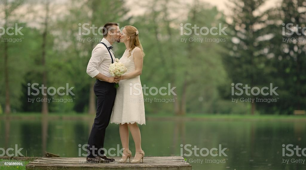 Bride and groom kissing near lake stock photo