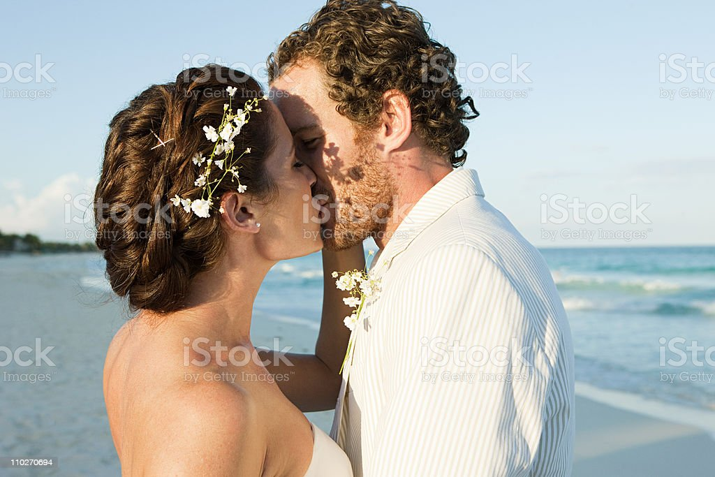 Bride and groom kissing on beach royalty-free stock photo
