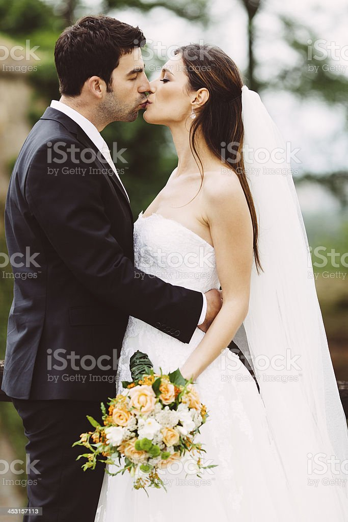 Bride and groom kissing outdoors. royalty-free stock photo