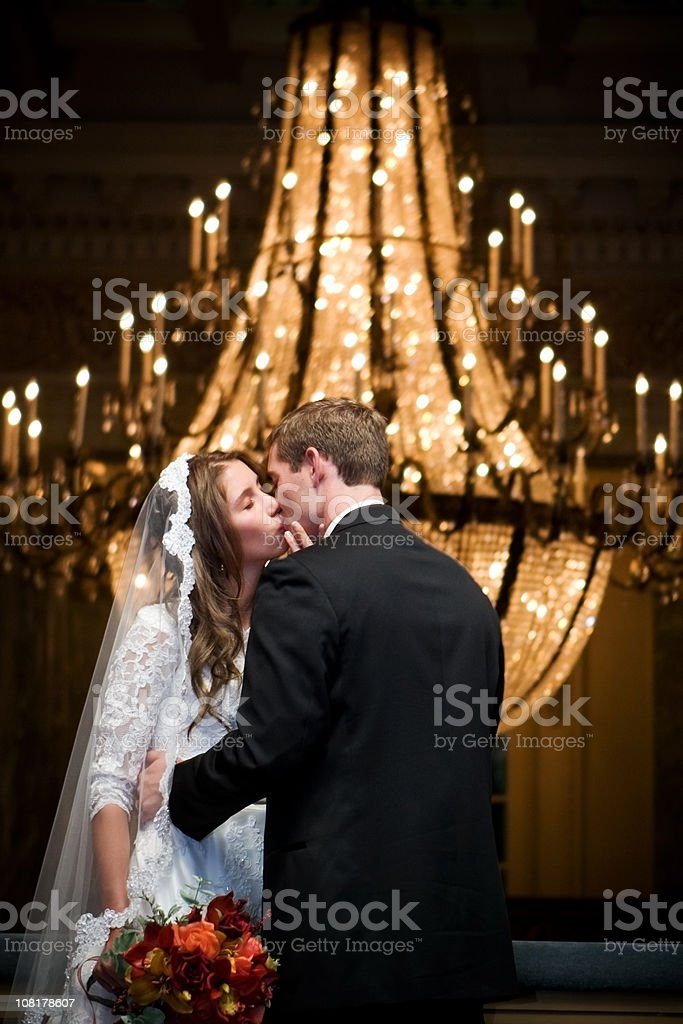 Bride and Groom Kissing with Elegant Chandelier royalty-free stock photo
