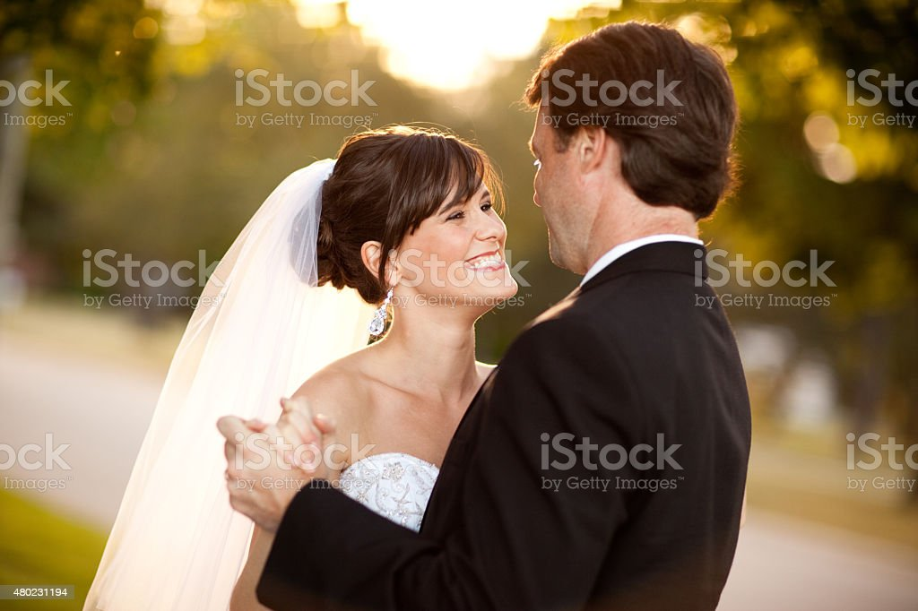 Bride and Groom Laughing and Dancing Together Outside stock photo