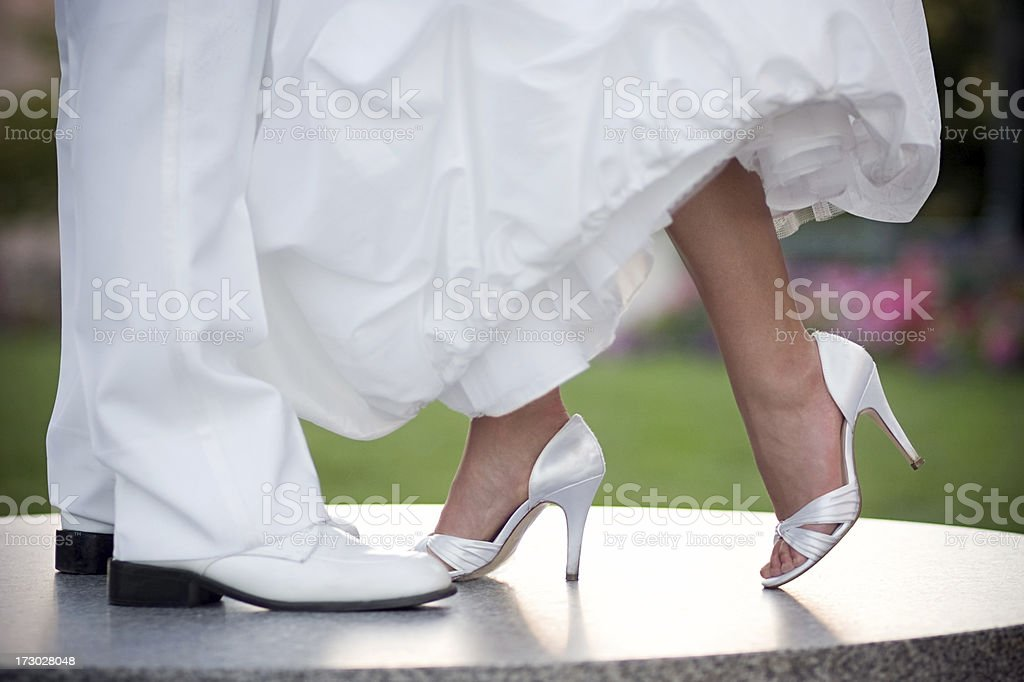 Bride and Groom Legs in White Wedding Gown Tuexedo Shoes stock photo