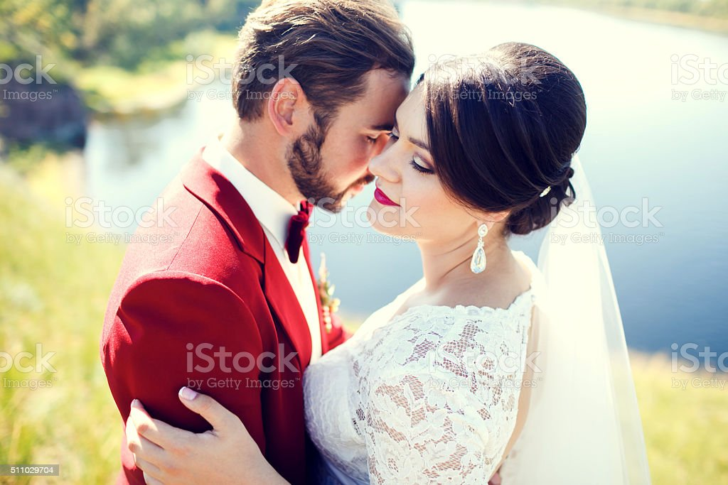 Bride and groom, lovely couple, cuddling on waterfront, photo shoot stock photo