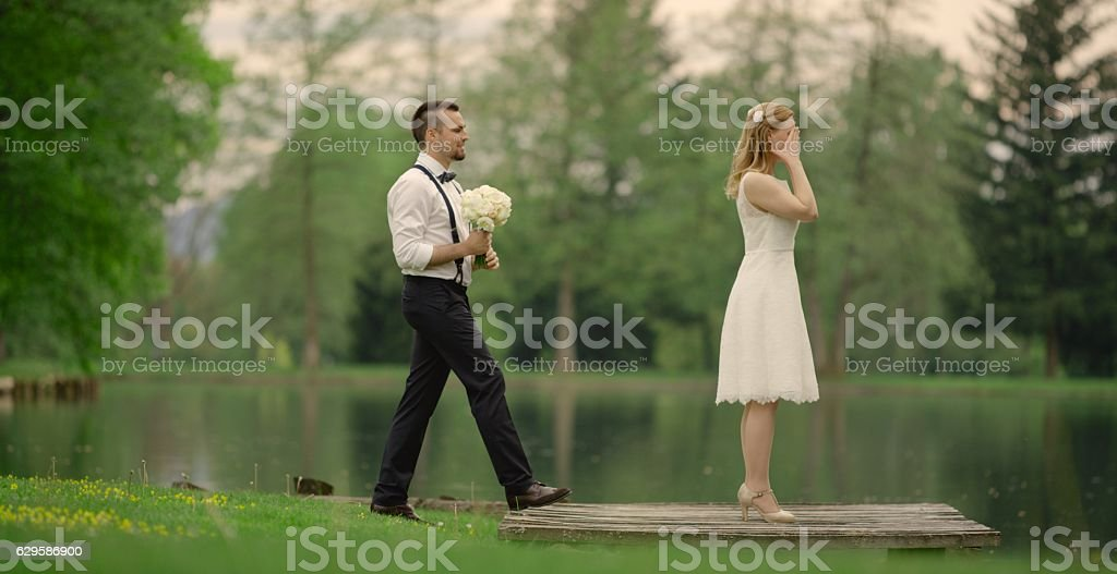 Bride and groom near lake stock photo