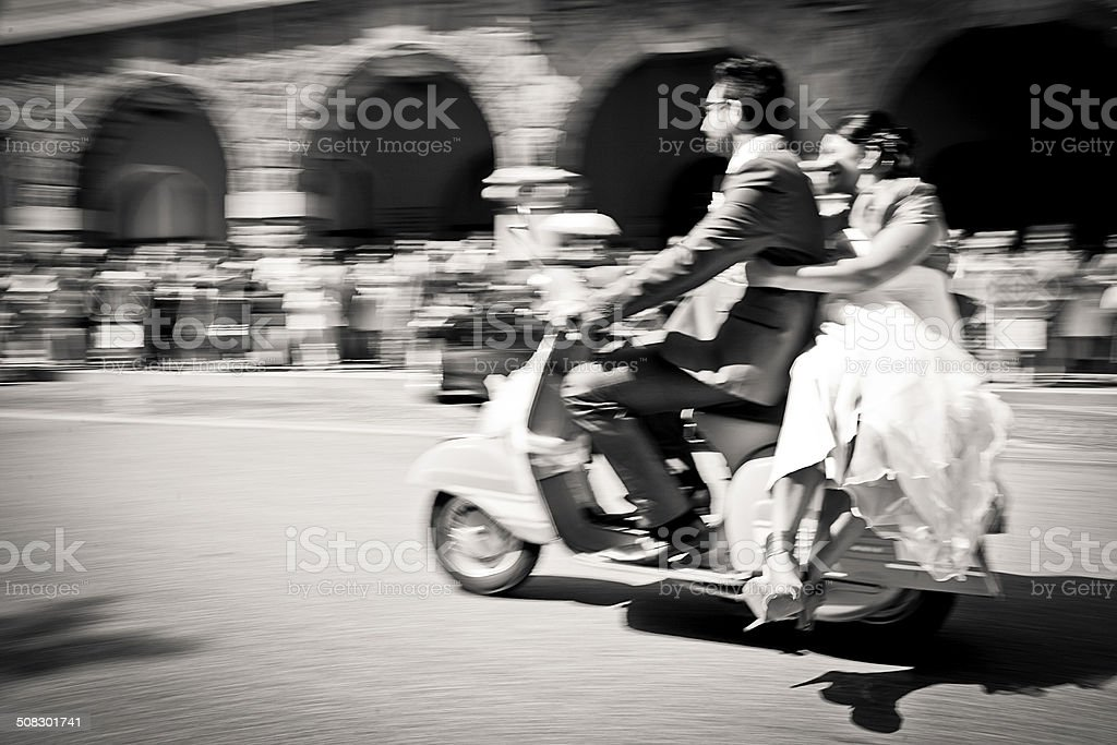 Bride and groom on a italian motor scooter stock photo