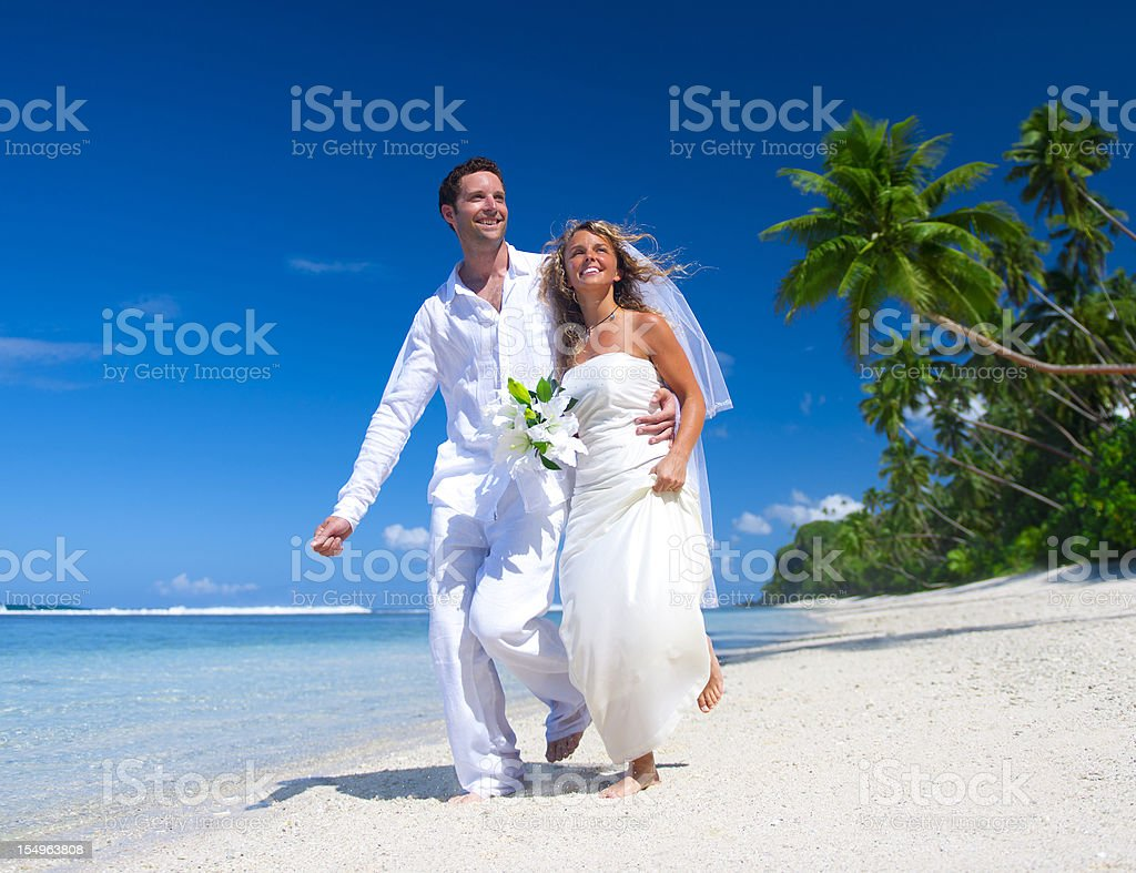Bride and Groom on an idyllic palm fringed beach royalty-free stock photo