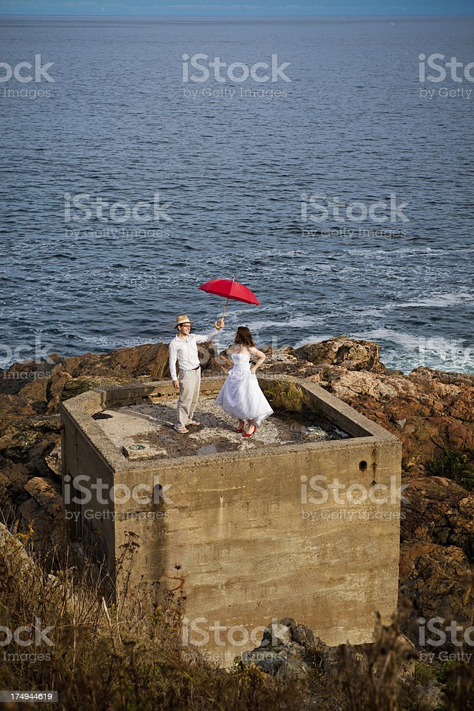 Bride and groom on concrete bunker with red umbrella royalty-free stock photo