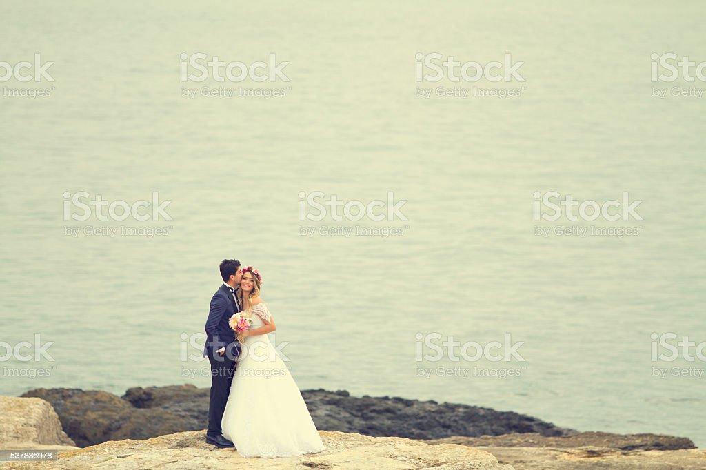 Bride and groom on rocks stock photo