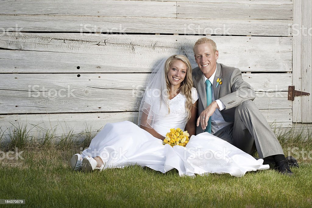 Bride and Groom Outdoors with Rustic Wooden Wall Background royalty-free stock photo
