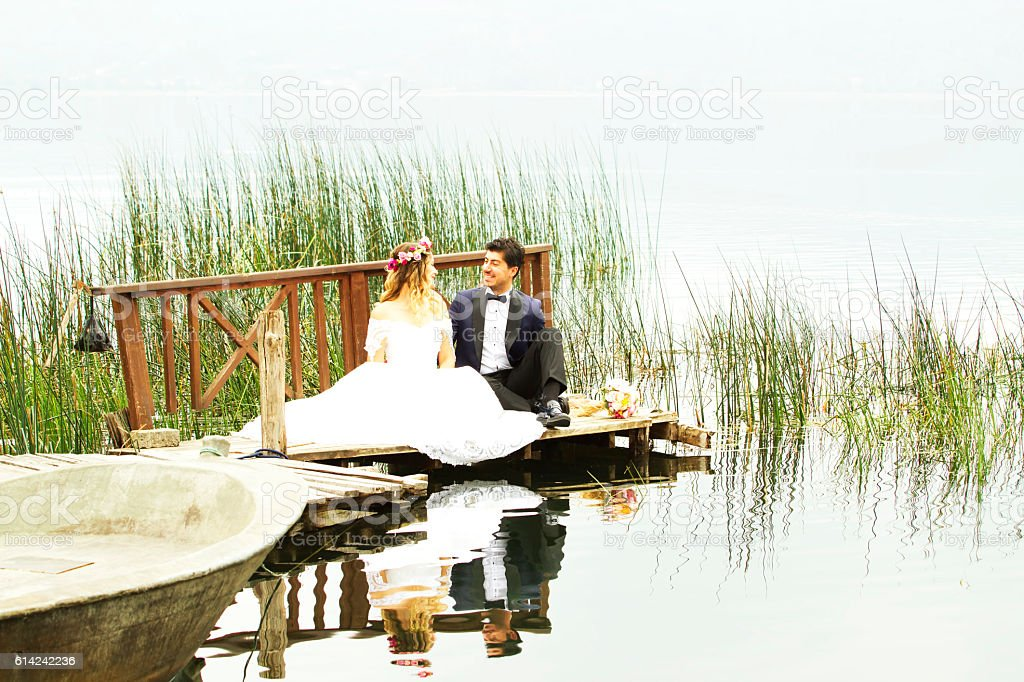 Bride and groom posing at a dock on the lake stock photo