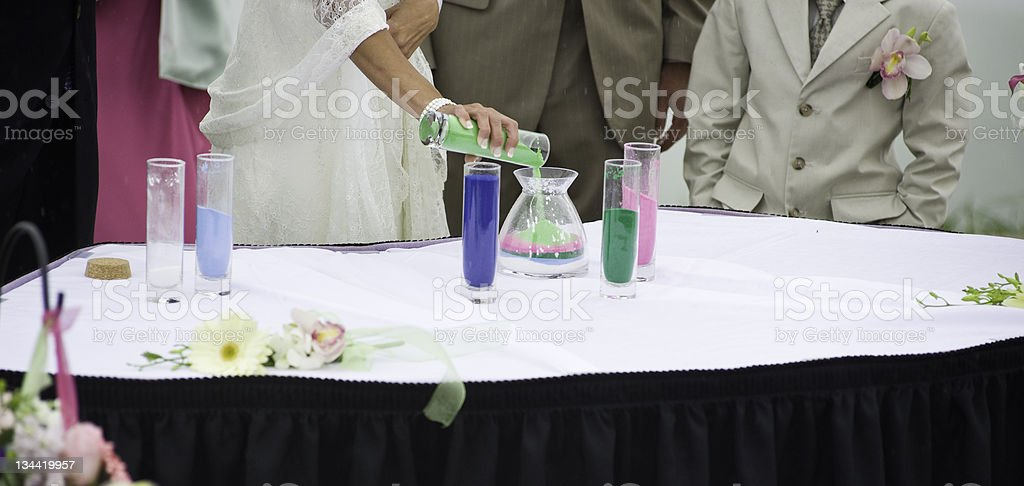 Bride and Groom Pouring Sand as Sign of Commitment royalty-free stock photo