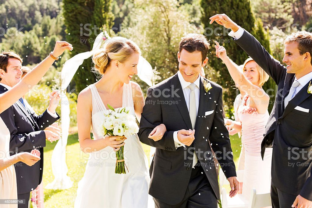 Couple Walking While Guests Throwing Confetti On Them stock photo