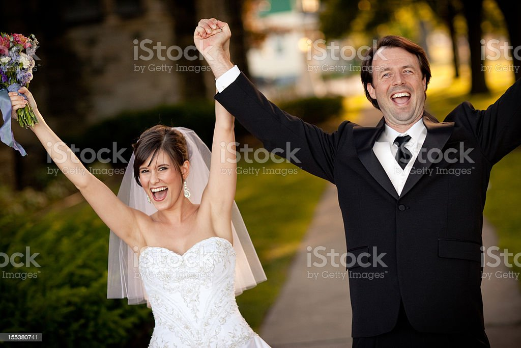Bride and Groom Raising Their Hands in Celebration stock photo