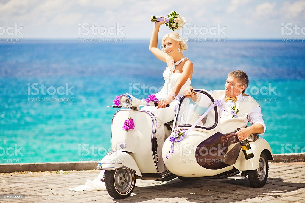 Bride and groom riding vespa on the beach stock photo