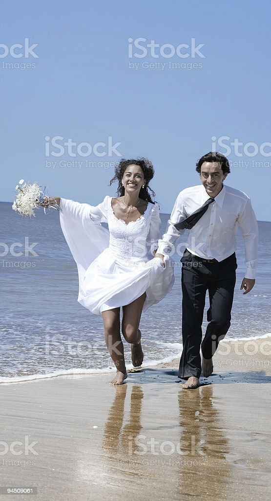 Bride and groom running at the beach stock photo