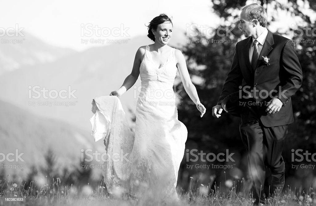 Bride and groom running through wildflowers royalty-free stock photo