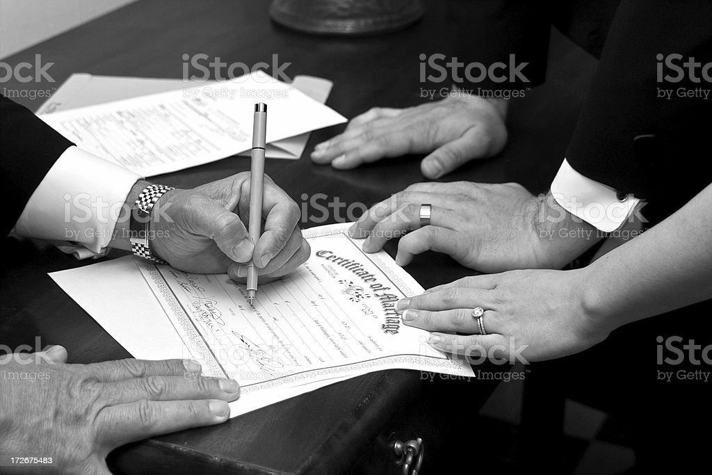 Bride and Groom Signing Marriage Certificate stock photo