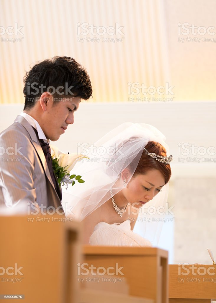 Bride and groom signing up in chapel stock photo