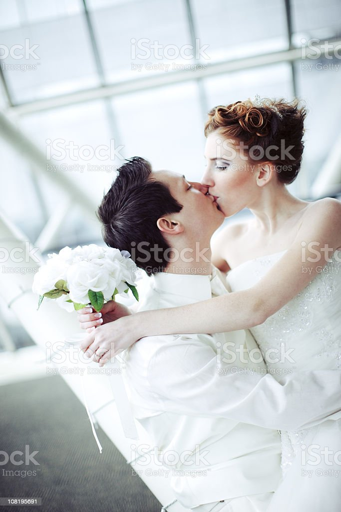 bride and groom sitting kissing royalty-free stock photo